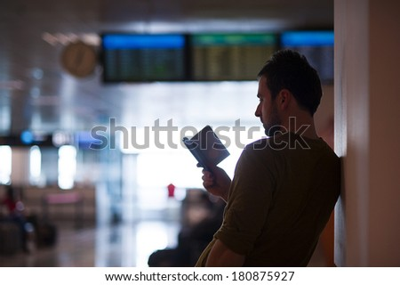 Young man is checking his passport in front of timeboard before going to gate.
