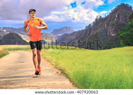 young man jogging through the fields