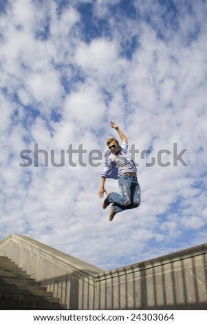 Young man jumping over  blue sky background