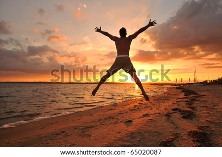 Young man jumping with spread arms celebrating and enjoying the moment at the seaside at sunset