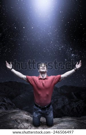 Young man knelt before a light from the sky