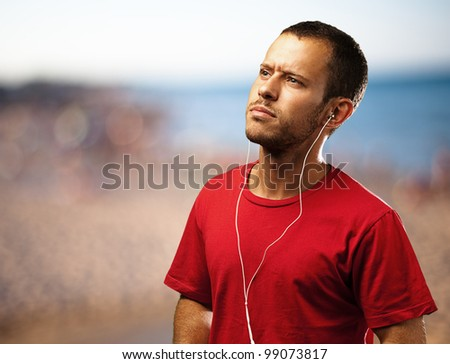 young man listen to music near the beach