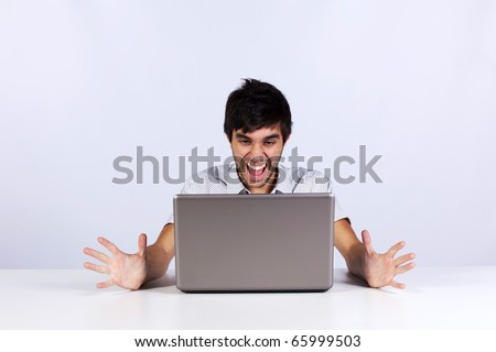 Young man looking to something terrible and screaming to his laptop