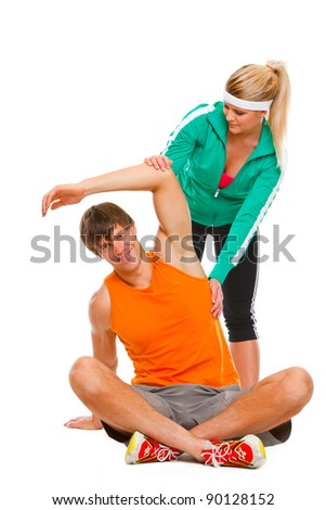 Young man making exercises on floor under the supervision of personal trainer