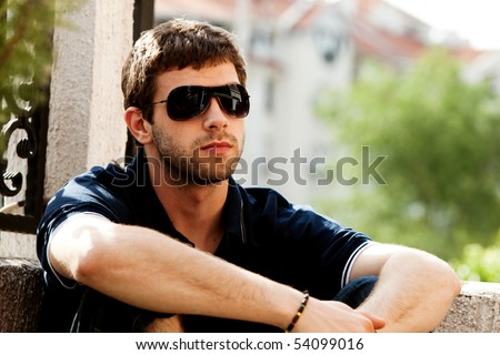 young man outdoor portrait with sunglasses