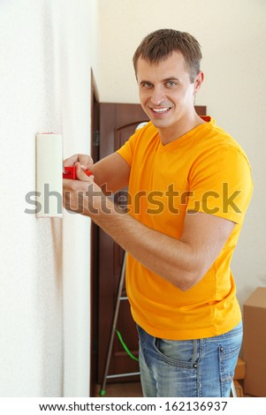 Young man paints wall in new flat