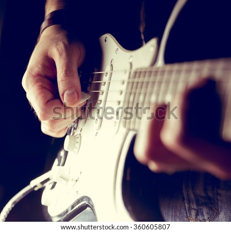 Young man playing electric guitar. Music, instrument education, entertainment, rock star, music concert   and learning concept