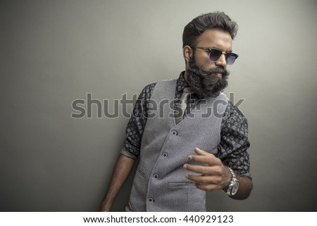 Young man posing with beard in suit with eye wear on grey background.