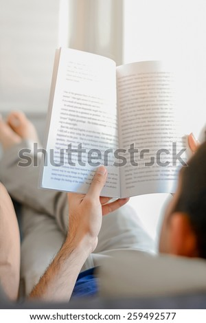 Young man reading book while lying on the couch - soft focus