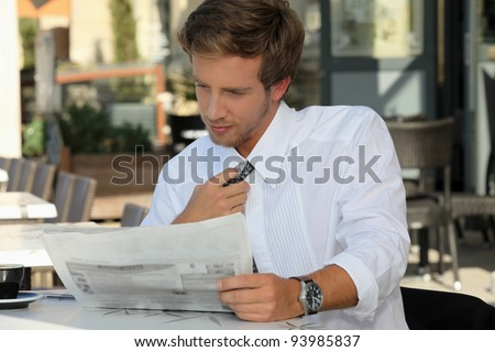 Young man relaxing reading newspaper