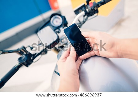Young man sitting on his motorcycle and holding phone above the bunker using touch screen in a soft focus background