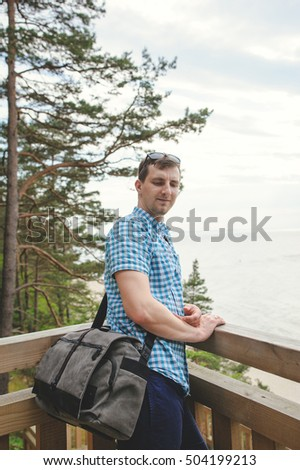 young man sitting on the wooden stairs in park and smiling