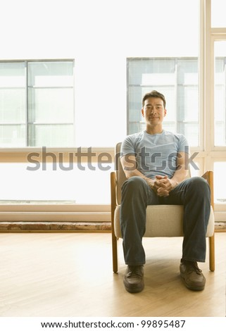 Young man sitting with hands folded