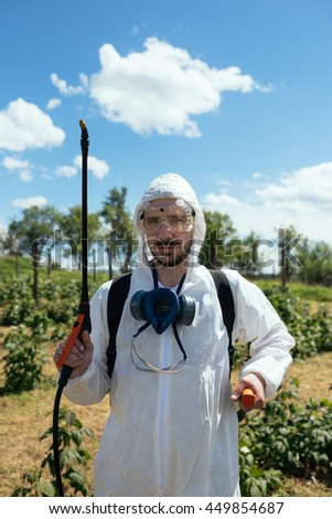 Young man spraying toxic pesticides or insecticides on fruit growing plantation. Natural light on hard sunny day. Blue sky with clouds in background.