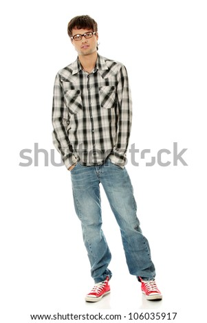 Young man standing with hands in pockets, wearing black glasses, plaid jeans and red sneakers. Isolated on the white background.