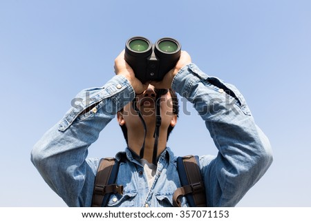 Young Man using binoculars with clear blue sky