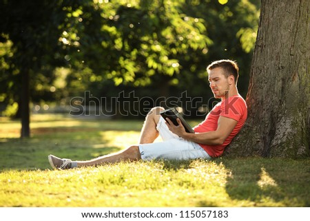 young man using tablet in park