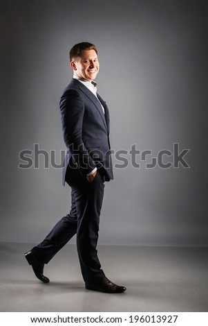 young man walking in black suit Full length