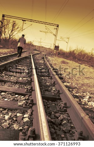 Young man walking on rail road