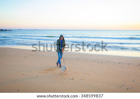 Young man walking with a dog on the beach at sunset in winter .
