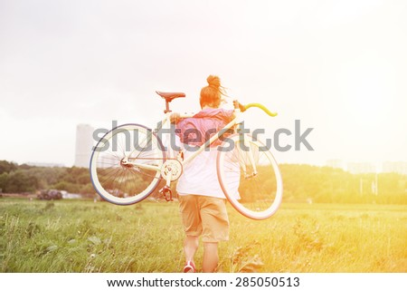 young man walking with bicycle in green field (intentional sun glare and bright colors)