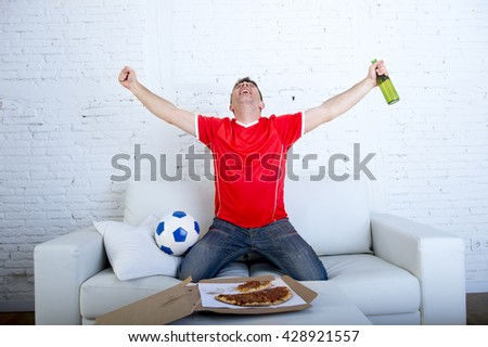 young man watching football game on television wearing team jersey celebrating goal crazy happy jumping on sofa couch at home with ball holding  beer bottle eating pizza excited