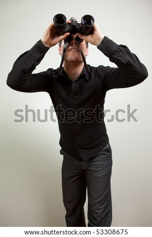 Young man wearing black shirt and holding binoculars, isolated on white