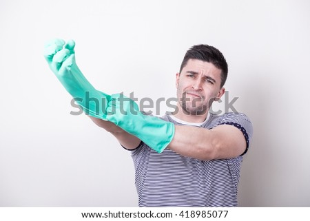 Young man wearing green rubber gloves. Ready to cleaning