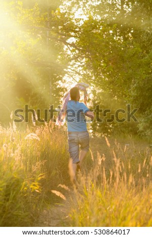 Young man with a headscarf jumps along the path in the woods, sunny