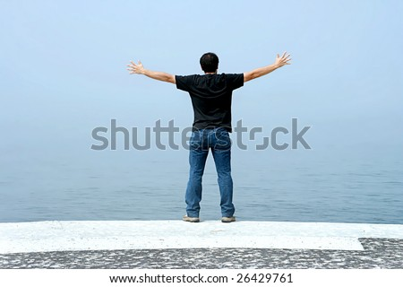 young man with arms open contemplating the ocean in foggy day