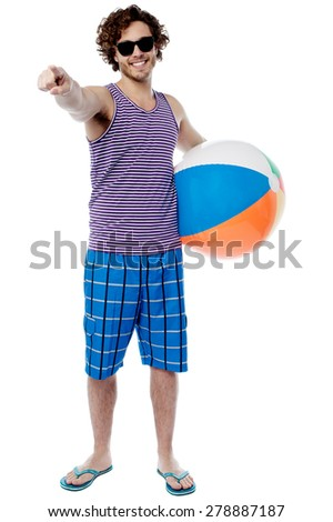 Young man with beach ball and pointing to camera