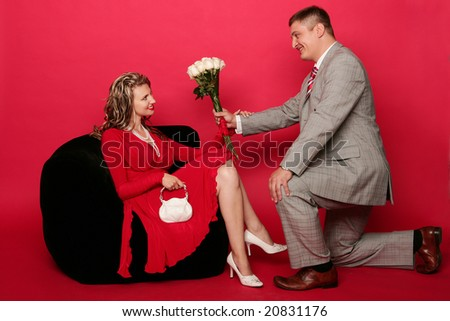 Young man with bouquet of roses stand on one knee in front of beautiful girl