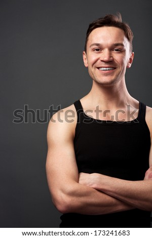 Young man with crossing arms against gray background