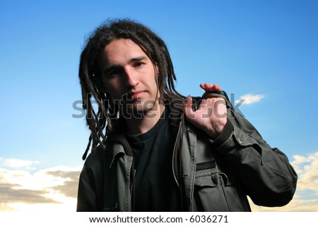 Young man with dreadlocks over blue sky