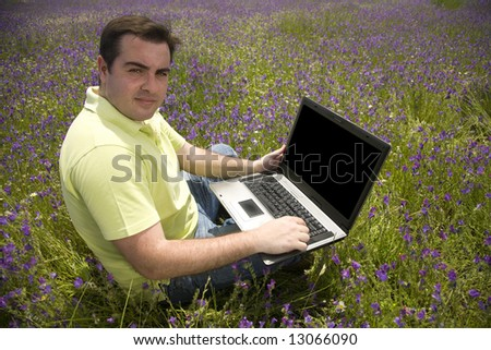 young man with laptop computer on a flower field