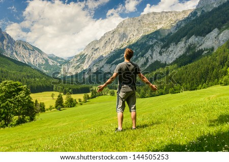 Young man with open arms charging energy from a nature.