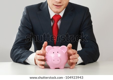 Young man with piggy bank (money box), isolated on white background