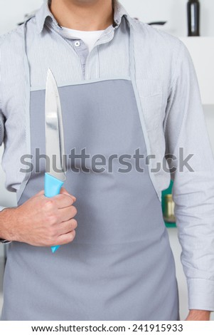 Young man with smock in a kitchen holding a knife