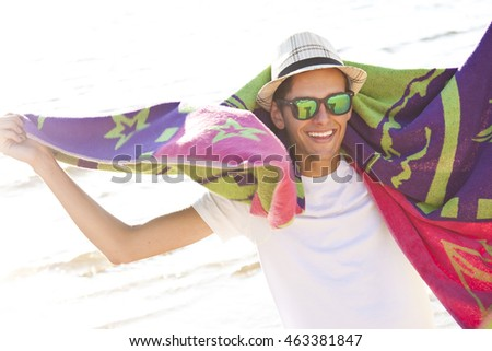 young man with the towel on the beach at sunset summer