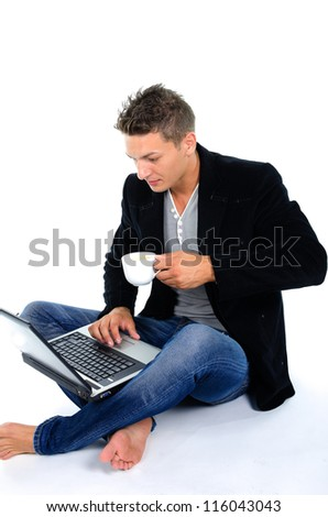Young man working at laptop and drinking coffee against white background