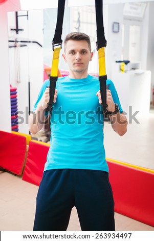 Young man working out with TRX in the gym.