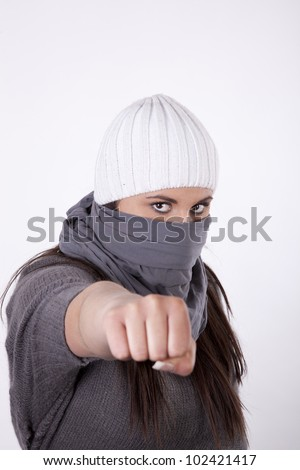 Young masked woman demonstrator holding fist.