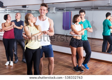 Young men and women dancing the salsa o bachata at the dance hall