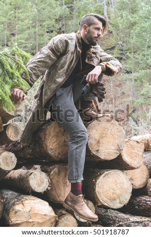 Young men on logs in the forest. Leather and jeans. Outdoor fashion
