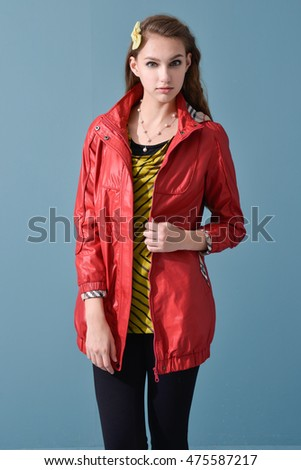 young model in red jacket dress posing on blue background