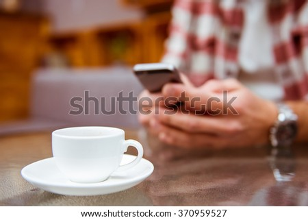 Young modern businessman in casual clothes using phone, sitting in a cafe and drinking coffee, close-up