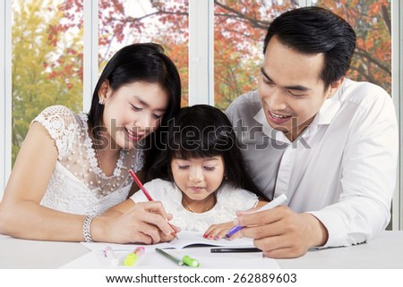 Young modern family assist their child doing schools assignment at home
