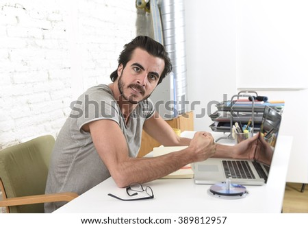 young modern hipster style student or businessman working with laptop computer at home office looking angry upset and stressed gesturing with fist frustrated in business stress concept