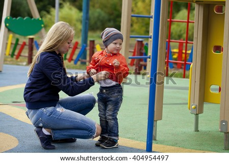 Young mother and baby boy playing on the playground in the autumn park