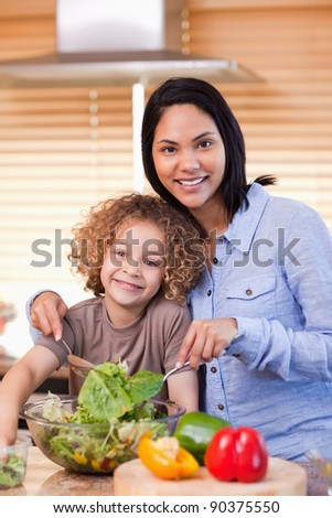 Young mother and daughter preparing salad in the kitchen together